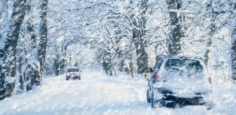 Two-cars-driving-on-snow-covered-road