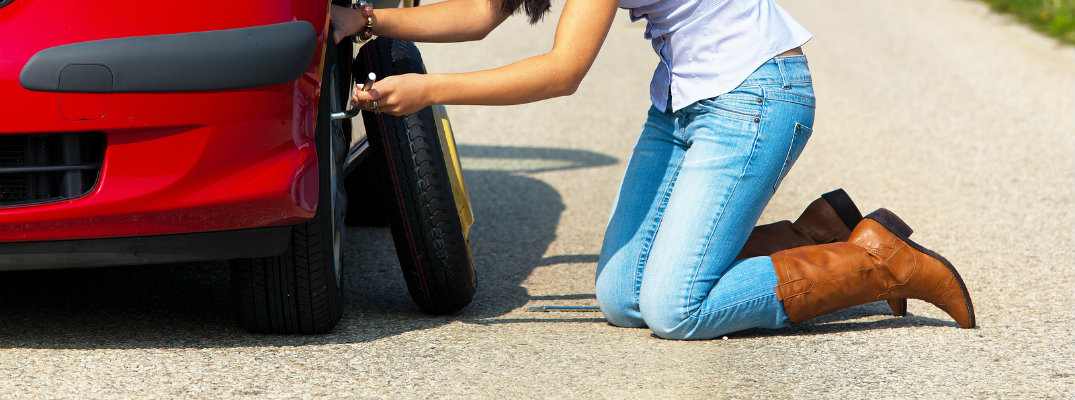 Young Woman Changing a flat tire on the highway