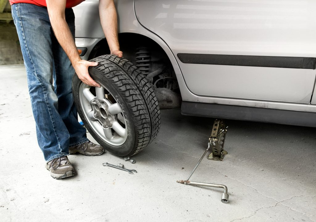 Man changes a tire on a gray car