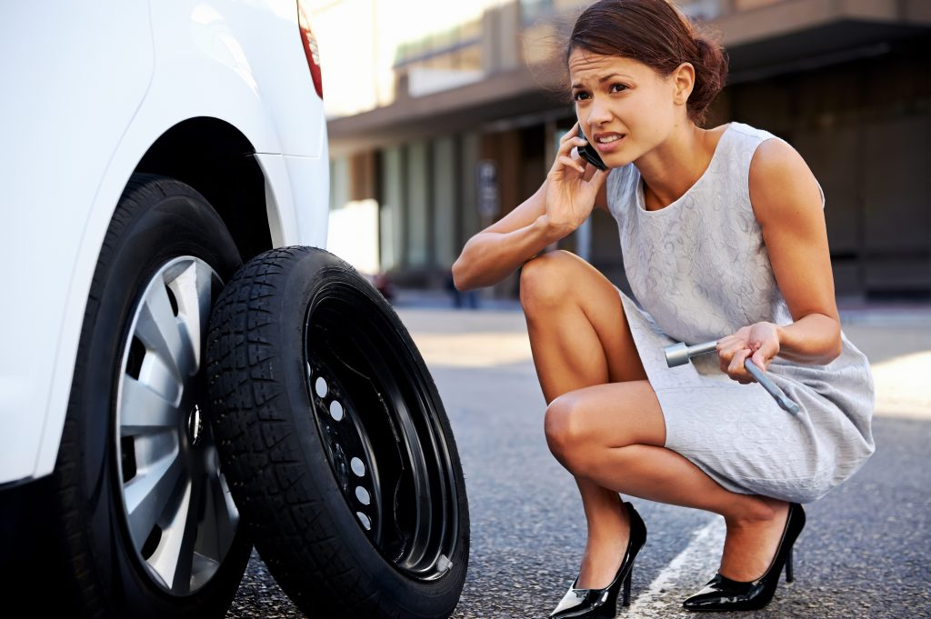 Woman calling for help with a flat tire in the city
