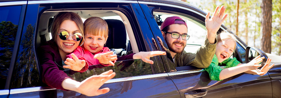 family leaning out of vehicle windows in woods