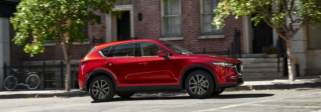 2018 Mazda CX-5 Exterior passenger side profile parked on road with trees and building background