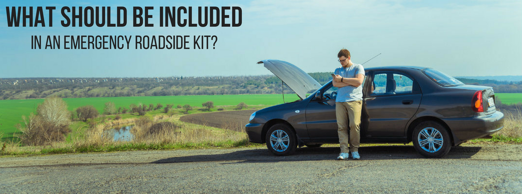 What Should Be Included in an Emergency Roadside Kit? Man Checks Phone While Waiting for Roadside Assistance