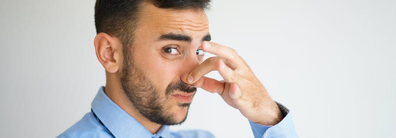 man plugging nose