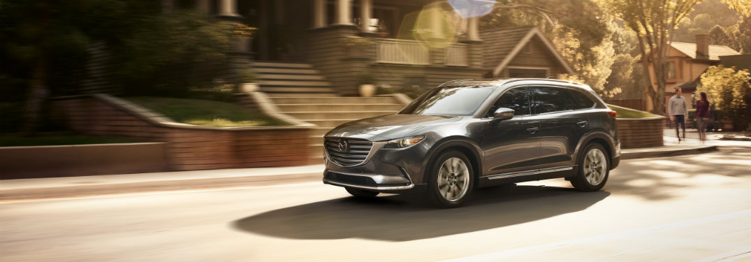 gray mazda cx-9 driving in front of houses