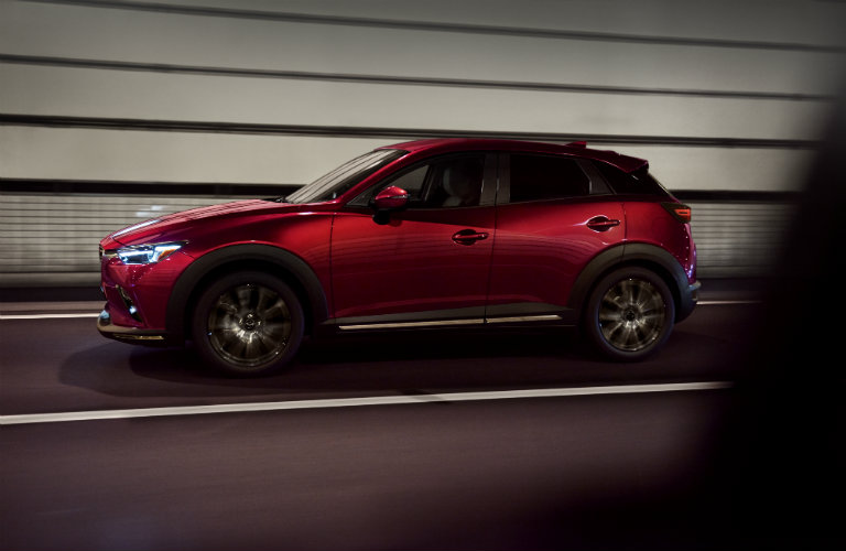 left side of red mazda cx-3 driving through tunnel
