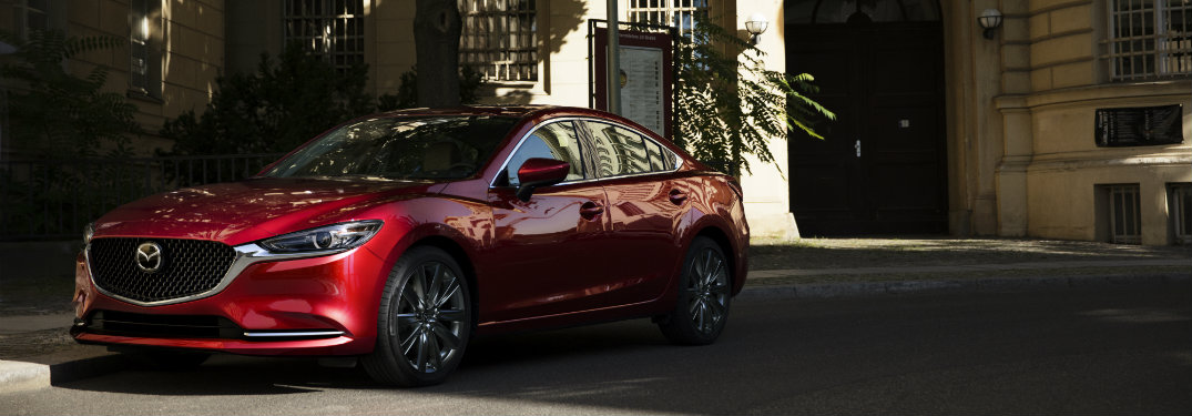front of red mazda6 driving in shadows