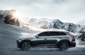 left side view of silver mazda cx-9 driving in snow