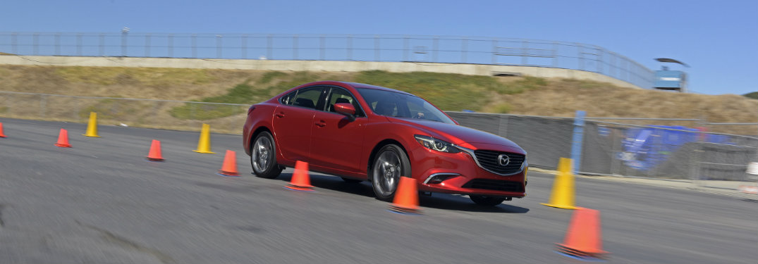 red mazda driving by orange cones