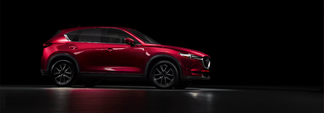 right side view of red mazda cx-5 parked in shadows