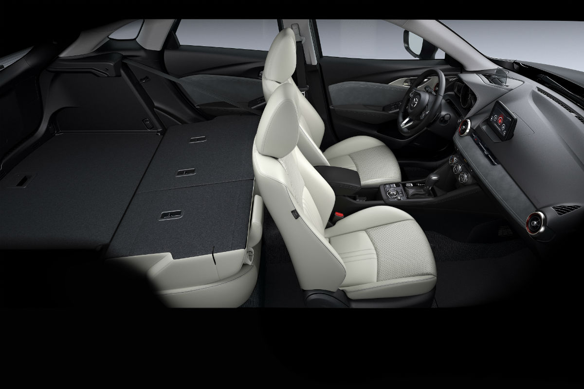 Side view of the rear seat of the 2019 Mazda CX-3 folded flat for cargo convenience