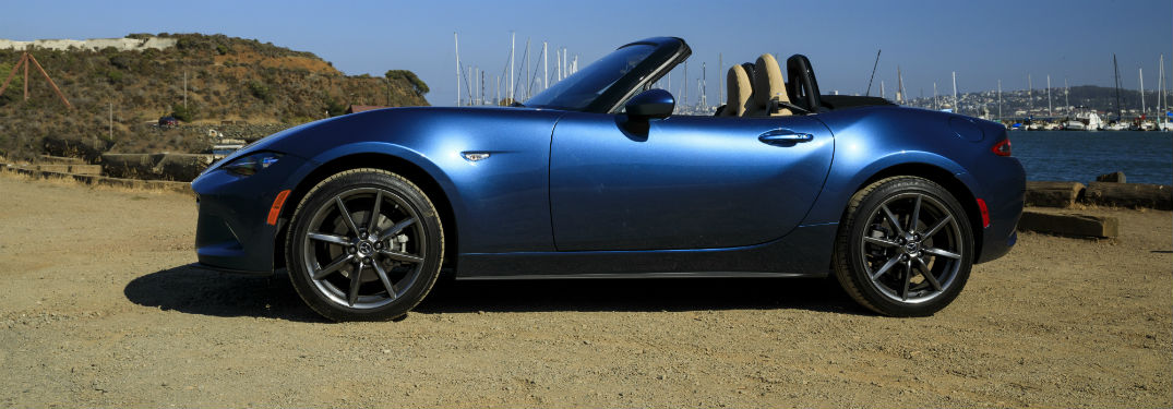 Driver side exterior view of a blue 2019 Mazda MX-5 Miata with its convertible top down