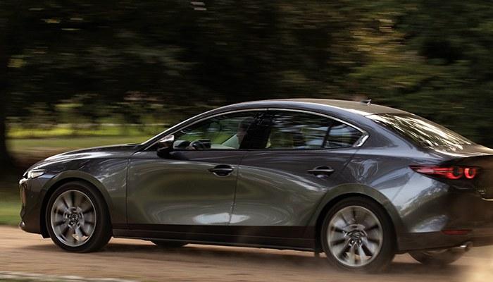 2020 Mazda3 Sedan driving down a rural trail