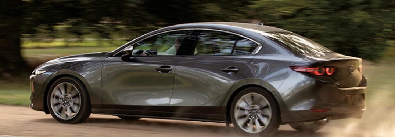2020 Mazda3 Sedan driving down a dirt road