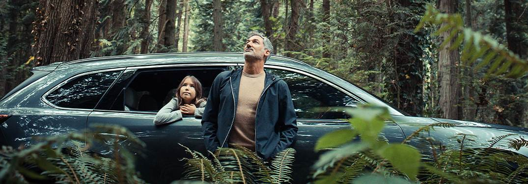 A man and young girl look at trees in a forest from a 2020 Mazda CX-9