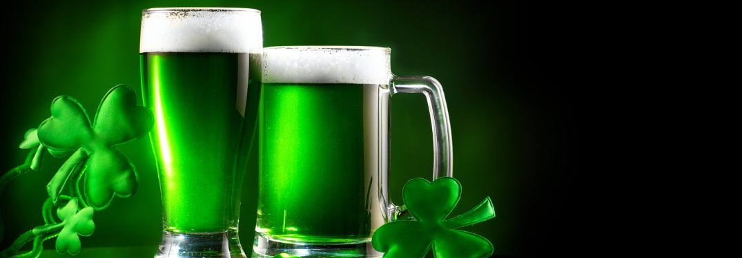 Green beer pints over a black background