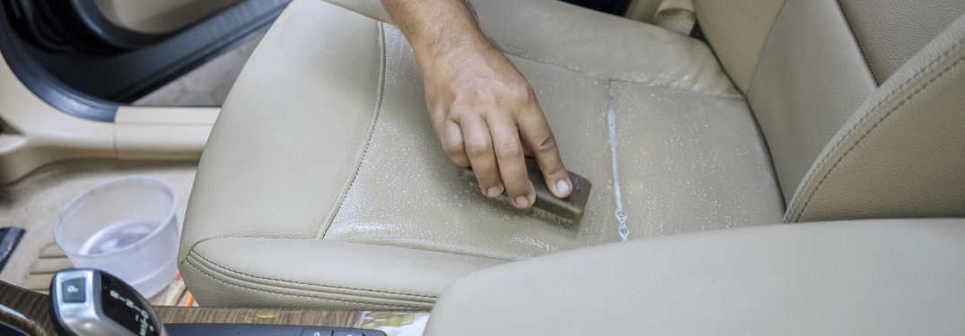 A hand cleaning up a car seat