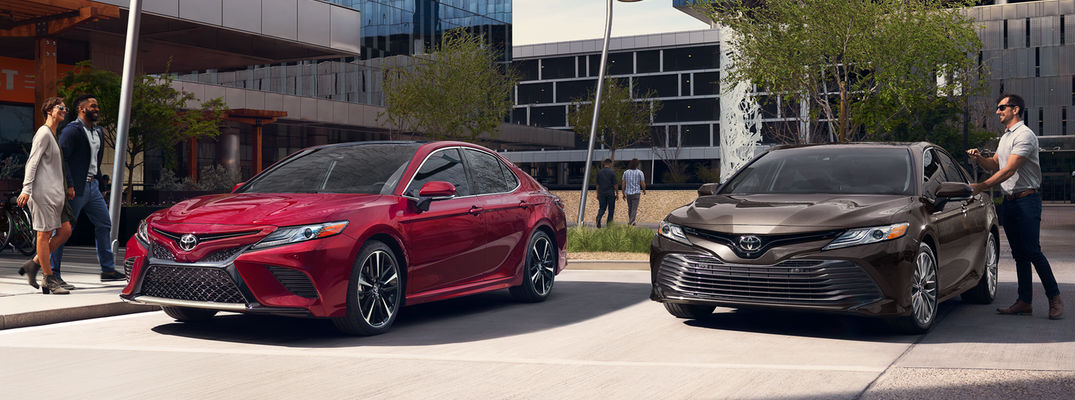 ... Ruby Flare Pearl And Brownstone 2018 Toyota Camry Models Parked By  Office Buildings