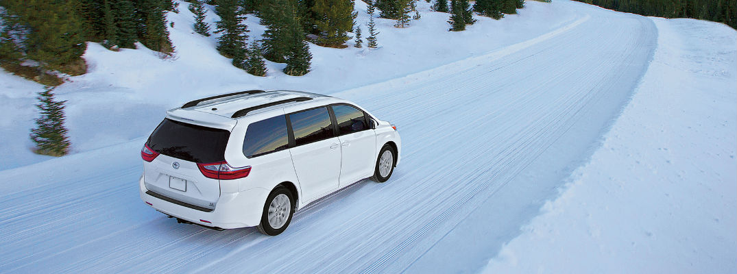 Toyota Sienna driving down a snowy road
