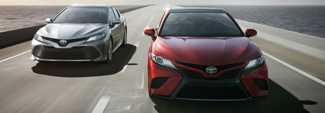 red and silver 2018 toyota camry models driving next to each other on highway bridge