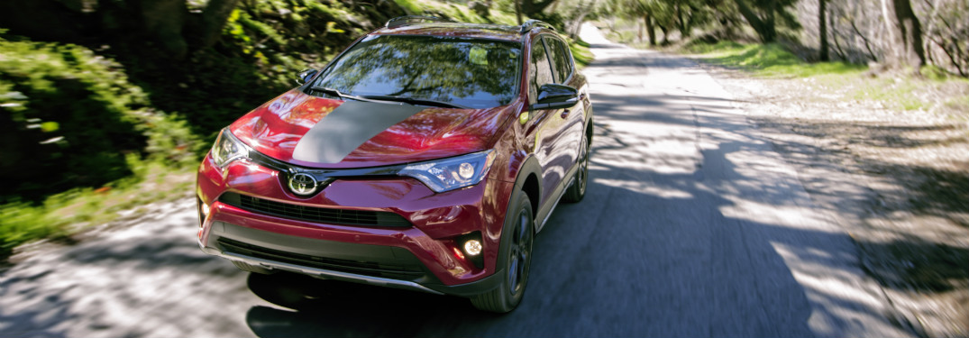 red 2018 toyota rav4 driving on suburban road