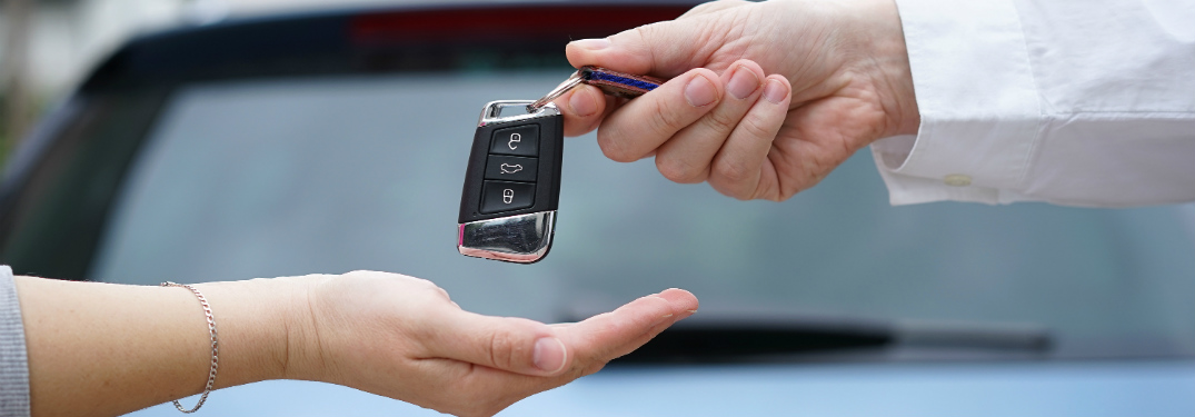 man handing over car keys to woman