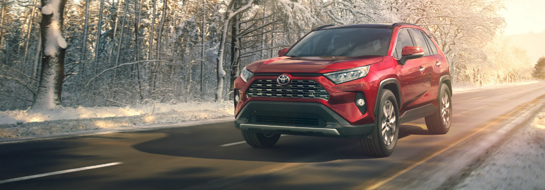 red 2019 toyota rav4 driving on road through snowy forest
