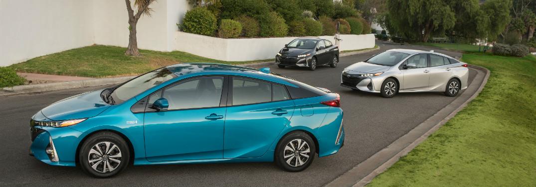 turquoise, white and silver 2018 toyota prius prime parked together in driveway of large hosue