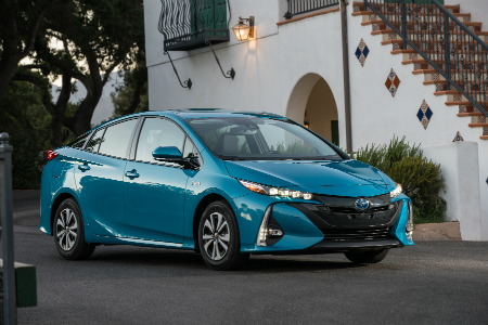turquoise 2018 toyota prius prime parked in driveway of white house