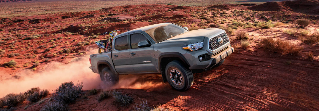 gray 2018 toyota tacoma ascending desert hill with dirtbike in cargo bed