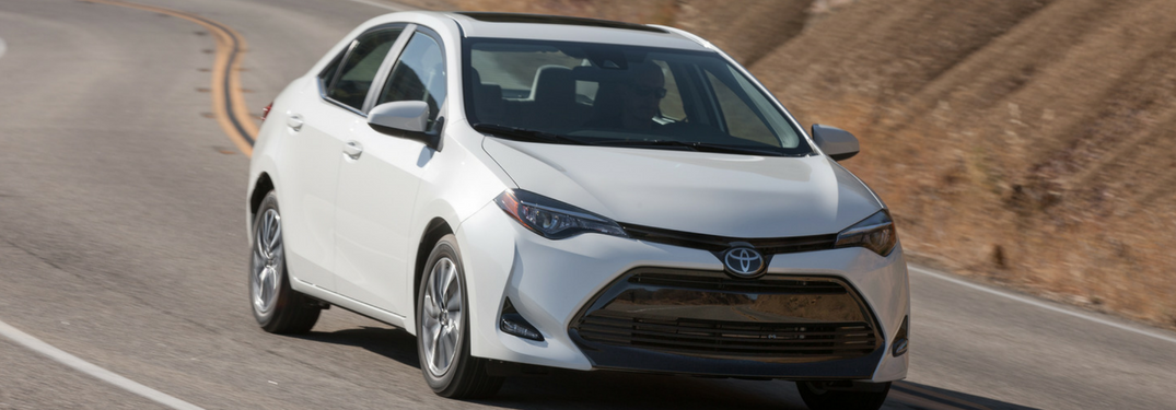 white 2018 toyota corolla driving down hill road