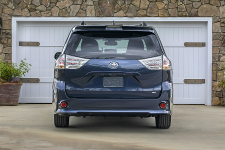 rear view of blue 2018 toyota sienna parked in driveway in front of white garage