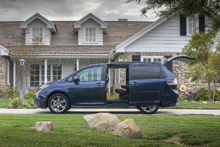 side view of blue 2018 toyota sienna in driveway of home with side cargo doors and rear lift gate open