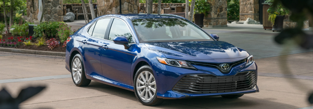 blue 2018 toyota camry parked in stone driveway surrounded by plants and trees