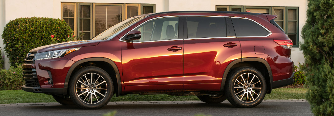 side view of red 2018 toyota highlander in front of white building and windows