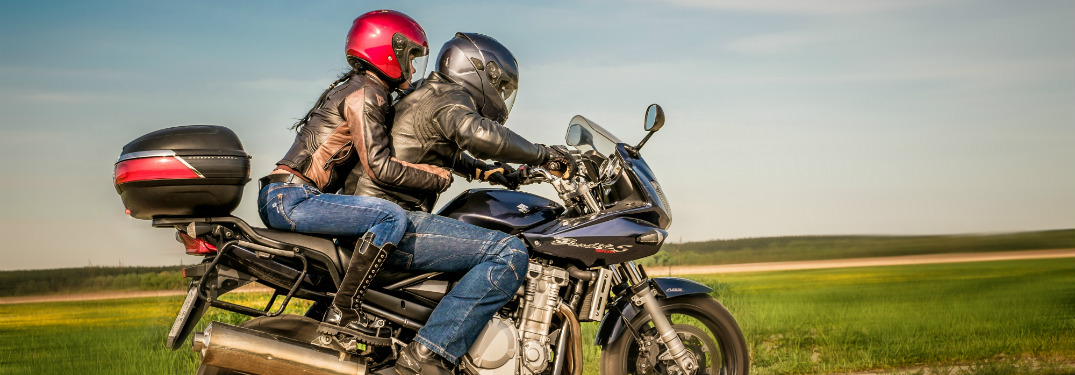 man and woman riding on motorcycle in open country road