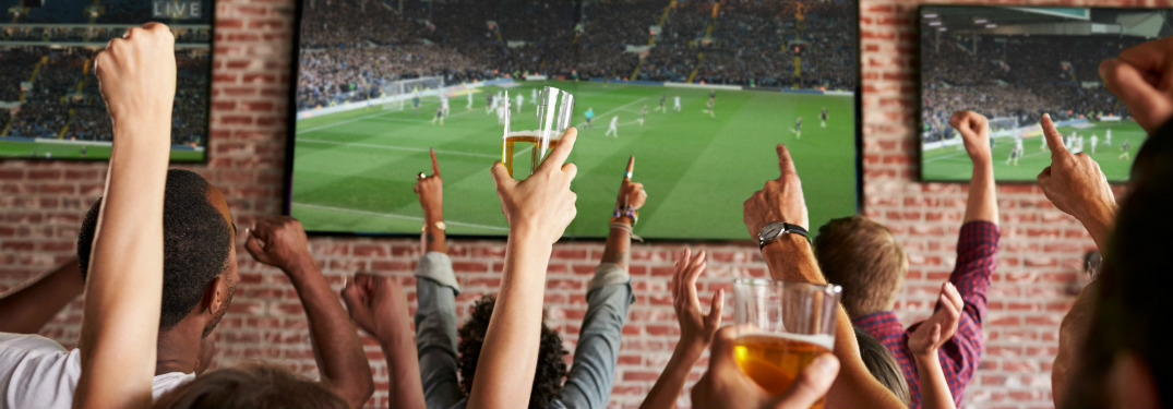 group of people at bar with hands in the air watching sports on tv