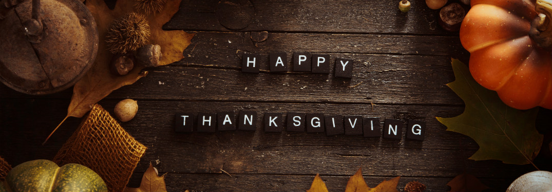 happy thanksgiving spelled out on black tiles on wooden table surrounded by fall decorations