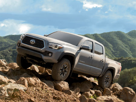 front and side view of gray 2019 toyota tacoma scaling rocks