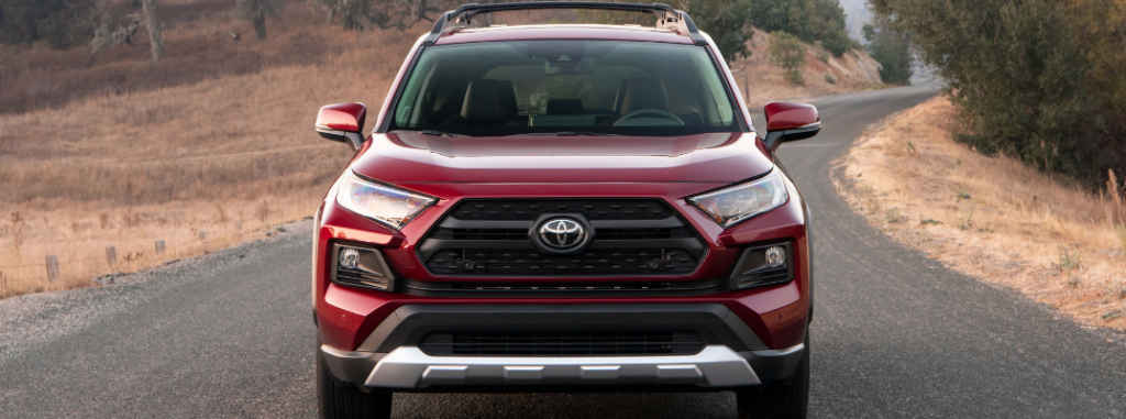 front view of red 2019 toyota rav4 including grille and headlamps