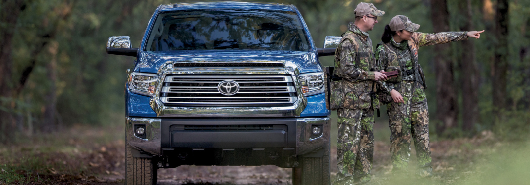 front view of blue 2019 toyota tundra with man and woman in camo gear next to it