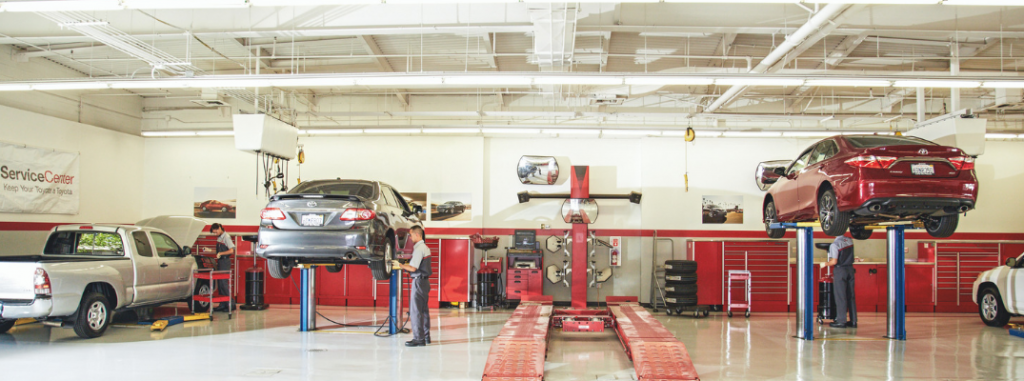 view inside toyota service center with raised cars and mechanics