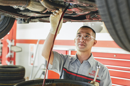 toyota service technician performing service on lifted vehicle
