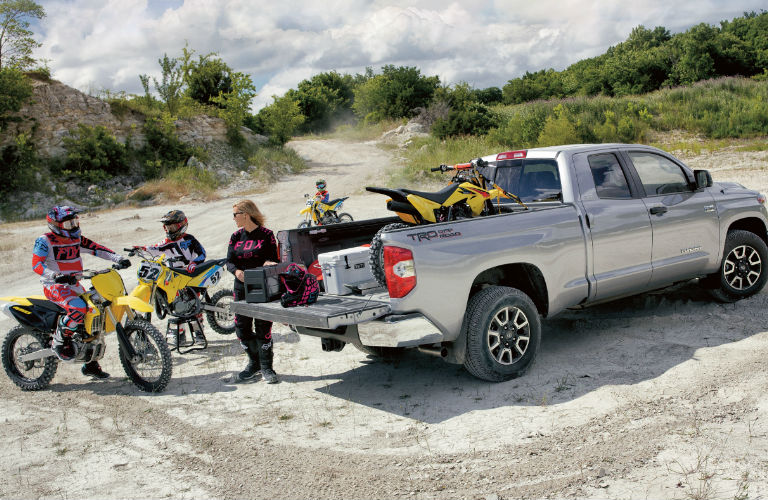2019 Toyota Tundra parked with family on dirt bikes behind it