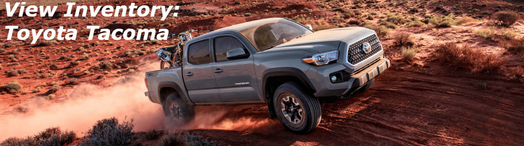 Toyota Tacoma driving up a hill on an off-road trail