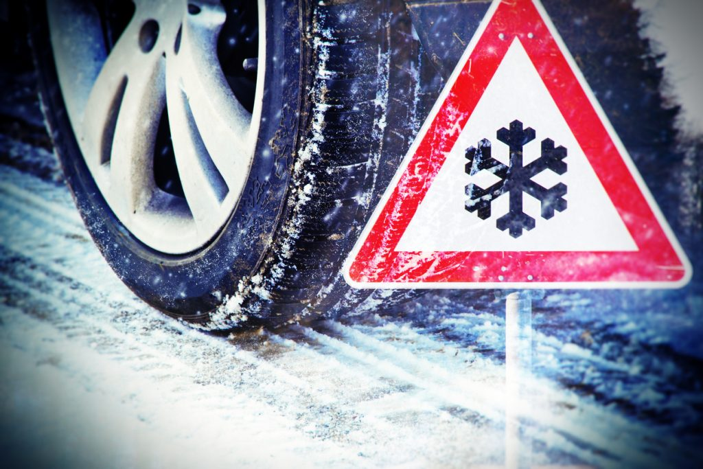 Car tires on winter road with traffic sign