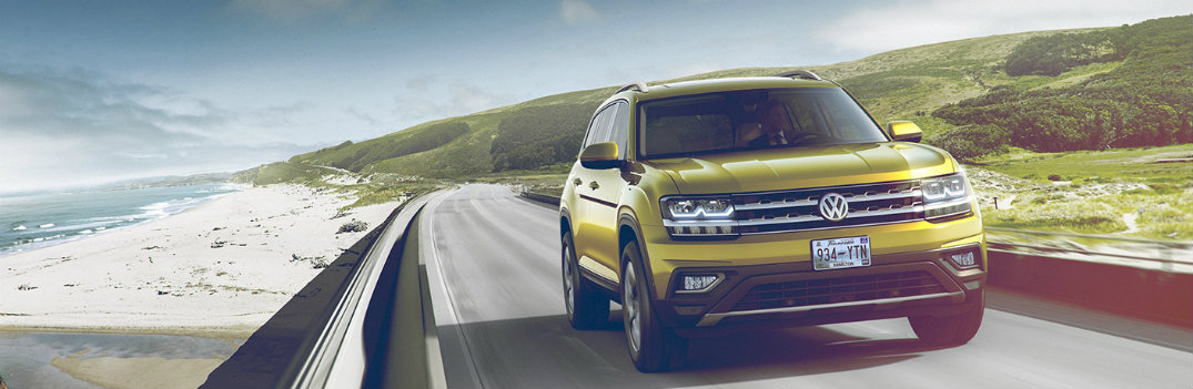 2018 Volkswagen Atlas driving on a highway next to grassy hill