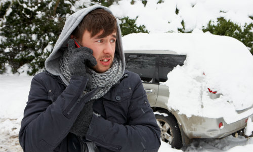 Man calling phone for help in the snow after car stops working