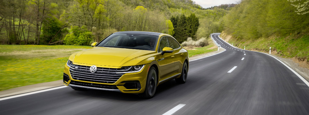 2019 Volkswagen Arteon R-Line appearance package exterior tumeric yellow paint shot driving down a curving country forest highway road