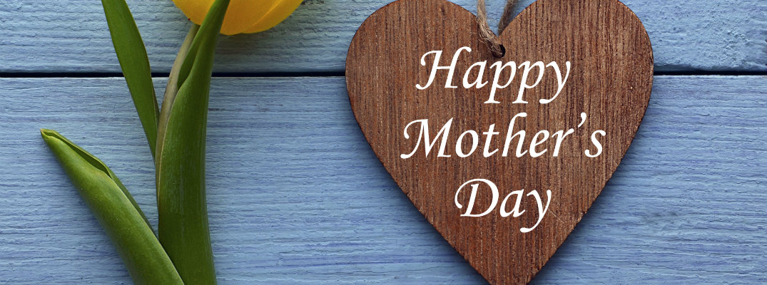 happy mother's day message carved on a wooden heart next to a yellow tulip flower in front of a blue painted house in the grass